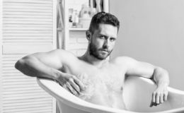 Cuerpo de limpieza de las piezas Huevo en tocador El torso muscular del hombre se sienta en ba?era Cuidado de piel Concepto higi? imagenes de archivo