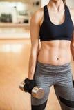 Cuerpo de una mujer con el ABS que lleva a cabo pesa de gimnasia Foto de archivo libre de regalías