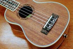 Cuerpo del ukelele marrón de madera del color en el fondo de madera real de la tabla Fotos de archivo libres de regalías