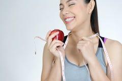 Cuerpo delgado de la mujer con la fruta de la manzana en el fondo blanco Fotos de archivo