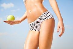 Cuerpo delgado perfecto de la mujer que sostiene una manzana. Fotografía de archivo libre de regalías