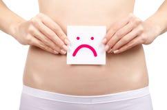 Cuerpo femenino de la salud de la mujer que celebra sonrisa triste de la tarjeta blanca cerca del estómago sana imagenes de archivo
