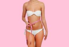 Cuerpo femenino sensual con la cinta métrica blanca del anda del bikini Imagenes de archivo