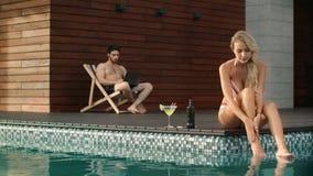 Cuerpo hidratante de la mujer alegre en poolside Pares felices que descansan sobre poolside metrajes