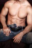 Cuerpo machista atractivo del hombre que se sienta en cama Foto de archivo libre de regalías