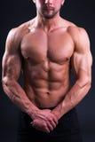 Cuerpo muscular hermoso del hombre joven que presenta sobre gris Fotografía de archivo