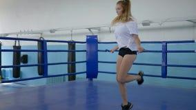 Cuerpo sano, deportista en cuerda de salto de los pantalones cortos en la cámara lenta en el ring de boxeo almacen de video