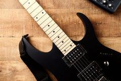 Cuerpo y fretboard de la guitarra eléctrica moderna en fondo de madera rústico imagenes de archivo
