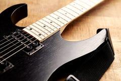 Cuerpo y fretboard de la guitarra eléctrica moderna en fondo de madera rústico imágenes de archivo libres de regalías