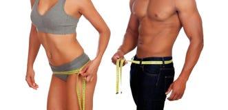 Cuerpos del hombre y de la mujer que miden la cintura con cinta métrica Imágenes de archivo libres de regalías