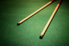 Cues for billiards. On green table, vignette stock image