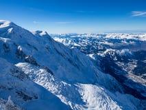 Cuesta de la nieve con la montaña contra el cielo azul y los picos escarpados de las montañas, Mont Blanc, Francia Imagenes de archivo