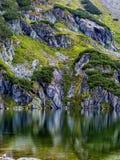 Cuesta de montaña con el pequeño lago en el botom foto de archivo