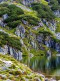 Cuesta de montaña con el pequeño lago en el botom fotografía de archivo
