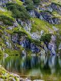 Cuesta de montaña con el pequeño lago en el botom imagenes de archivo