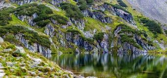 Cuesta de montaña con el pequeño lago en el botom fotos de archivo