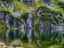 Cuesta de montaña con el pequeño lago en el botom imagen de archivo