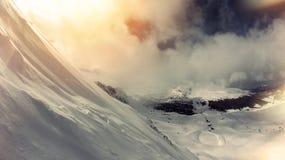 Cuesta de montaña, mucha nieve, la visión a través de las nubes Paisaje del invierno Foto de archivo