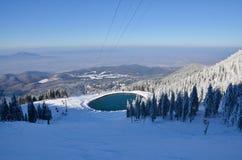Cuesta del esquí en la mucha altitud, y un lago, paisaje del invierno Fotografía de archivo libre de regalías