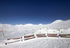 Cuesta del esquí y bancos de madera en nieve Imagen de archivo libre de regalías