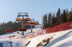 Cuesta del esquí y remonte moderno de la silla Fotografía de archivo