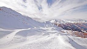 Cuesta del esquí en montañas nevosas Imagenes de archivo