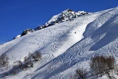 Cuesta fuera de pista con la pista del esquí y snowboard el día soleado Fotografía de archivo libre de regalías
