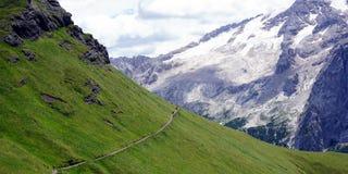 Cuesta verde al contrario de picos nevosos en dolomías Foto de archivo