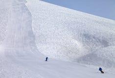 Cuesta y esquiadores del esquí en el día del sol Imagen de archivo