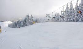 Cuesta y telesilla del esquí entre bosque spruce en estación de esquí Imágenes de archivo libres de regalías