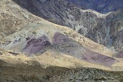 Cuestas de montaña de colores brillantes: en las rocas violetas del primero plano, roca del gris del fondo Fotografía de archivo