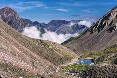 Cuestas de montaña con el talud de piedra y un pequeño lago Imagenes de archivo