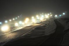 Cuestas del esquí en la noche fotos de archivo