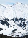 Cuestas escarpadas del esquí con la aldea imagenes de archivo