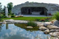 Cueva artificial en el jardín como cocina al aire libre y roo que se sienta imagen de archivo libre de regalías