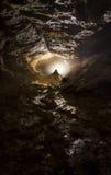 Cueva con la luz y la estalagmita Fotos de archivo
