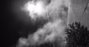 Cueza al vapor contra la luz en la noche, tiro blanco y negro místico de la linterna de la calle almacen de metraje de vídeo