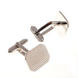 Cuff links. A pair of silver colored cuff links, isolated on white royalty free stock photography