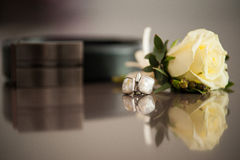 Cuff-links and belt with yellow rose. Reflection on a merble table Royalty Free Stock Image