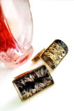 Cuff links and bottle of perfume on a white background. Two objects close up and fragment of a bottle of perfume. Indoors. Vertical format. Color. Photo stock images