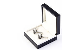 Cuff links in a box. Mens cuff links in a black box isolated on a white background stock images