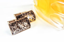 Cuff links on a white background with a bottle of perfume of yellow color. The isolated objects on a white background with a shadow. Horizontal format. Color stock photo