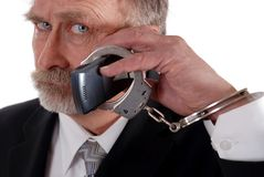 Cuffed to phone. Business man handcuffed to his cell phone Stock Image