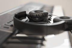 Cuffia avricolare cablata sopra la tastiera di piano elettronica Immagine Stock Libera da Diritti