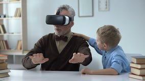 Cuffia avricolare d'uso del vr del nonno, contentissima con le nuove tecnologie, svago con il bambino video d archivio