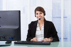 Cuffia avricolare d'uso della donna di affari allo scrittorio del computer Fotografia Stock Libera da Diritti