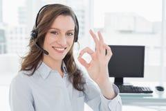 Cuffia avricolare d'uso della donna di affari mentre gesturing okay firmi dentro l'ufficio Immagini Stock Libere da Diritti
