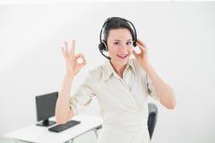 Cuffia avricolare d'uso della donna di affari mentre gesturing segno giusto Fotografie Stock Libere da Diritti