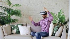 Cuffia avricolare d'uso di realtà virtuale del giovane uomo allegro che ha video esperienza di 360 VR mentre sedendosi sullo stra fotografie stock