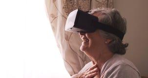 Cuffia avricolare d'uso di realtà virtuale della donna senior stock footage